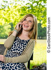 Laughing teenage girl talking on the phone