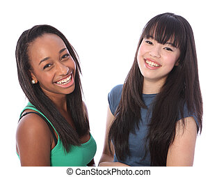 Laughing out loud are two happy beautiful teenage friends, a mixed race african american and oriental Japanese girls with big smiles and long black hair.