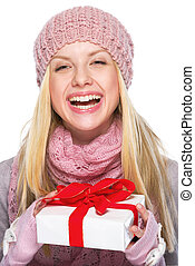 Laughing teenager girl in winter hat and scarf holding present