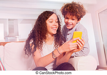 Laughing teens surfing internet using cell phone