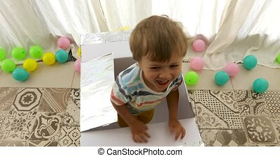 Laughing toddler in striped T-shirt getting out of gift box...