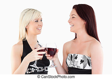 Laughing well-dressed women toasting with red wine