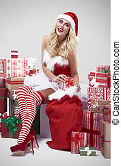 Laughing woman and a pile of Christmas gifts
