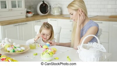 Laughing woman and little girl coloring eggs