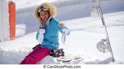 Laughing woman chatting on her mobile in snow
