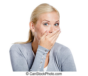 Laughing woman covers mouth with hand