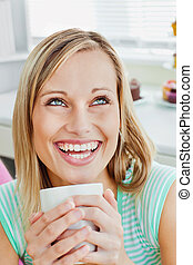 Laughing woman holding a cup of coffee at home