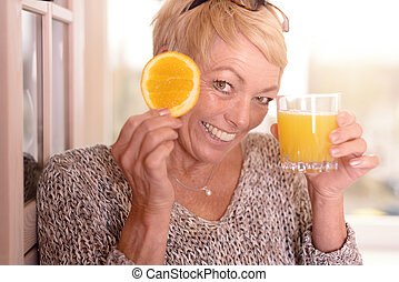 Laughing woman holding an orange to her eye