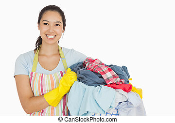 Laughing woman holding laundry basket wearing apron and rubber gloves