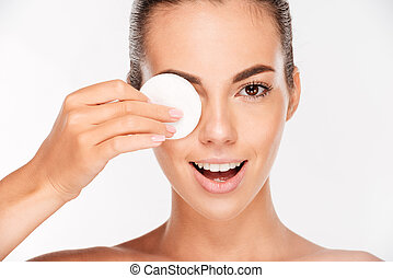 Laughing woman holding round white cotton pad to her eye - ...