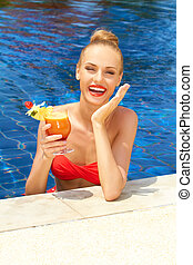 Laughing woman in a pool with a cocktail