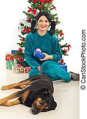 Laughing woman in pajamas hold Xmas gift