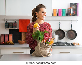 Laughing woman in profile, fall fruit and vegetables in...