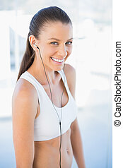 Laughing woman in sportswear listening to music