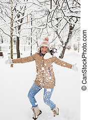 Laughing woman jumping in snow