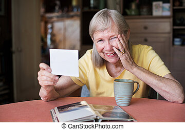 Laughing woman looking at photo - Blushing woman holding...