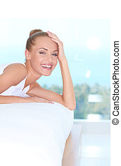 Laughing woman looking over back of sofa