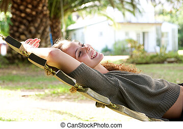 Laughing woman lying in hammock outside of house