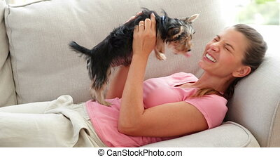 Laughing woman playing with dog