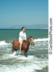 Laughing woman rides horse in water sea