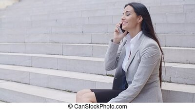Laughing woman sitting on steps with phone