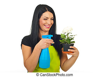 Laughing woman spraying flower in pot - Laughing woman...
