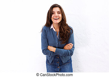 Laughing woman standing with arms crossed on white wall