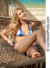 Laughing woman suntanning in a hammock