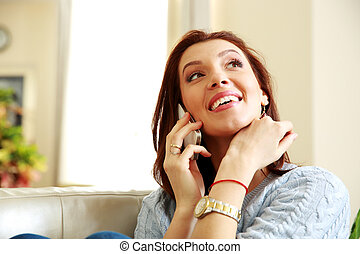 Laughing woman talking on the phone at home