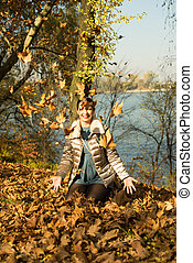 Laughing woman tossing leaves