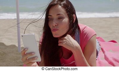 Laughing woman using phone at beach