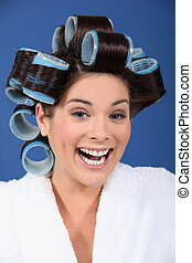 Laughing woman with her hair in Velcro rollers