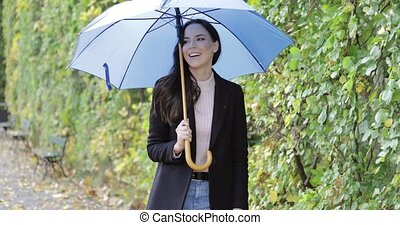 Laughing woman with umbrella - Attractive woman in black...