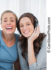 Laughing women listening to music