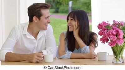 Laughing young adult couple sitting at table