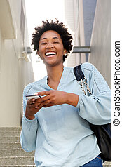 Laughing young african lady with mobile phone