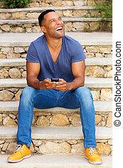 Laughing young african man sitting on stairs outdoors with cell phone and looking away