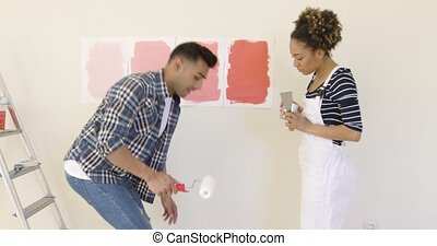 Laughing young couple choosing a paint color to renovate...