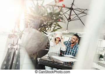 Laughing young lady covering face with paper while cheerful bearded man looking at her