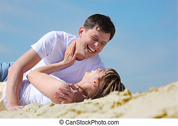 Laughing young pair lying on sand