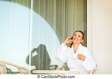 Laughing young woman in bathrobe with cup of coffee speaking mobile phone on terrace