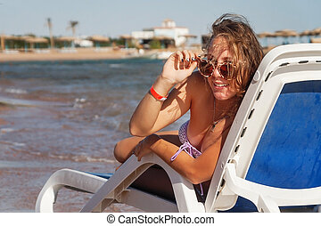 Laughing young woman in sunglasses sitting in a deckchair, against the background of the sea and tropical beach with palm trees
