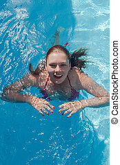Laughing young woman in the pool, close-up portrait
