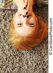 Laughing young woman lying on the carpet at home