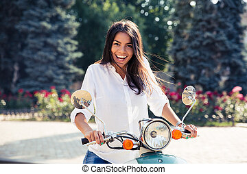Laughing young woman on scooter