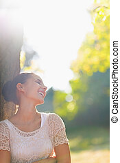 Laughing young woman relaxing in forest