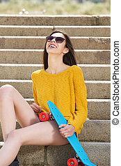 Laughing young woman sitting on steps with skateboard