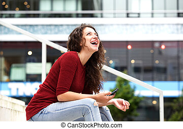Laughing young woman sitting outside with mobile phone
