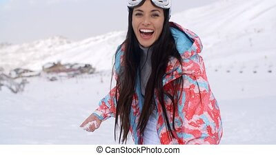 Laughing young woman throwing a snowball - Laughing...