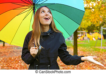 Laughing young woman with colorful umbrella checking for rain.